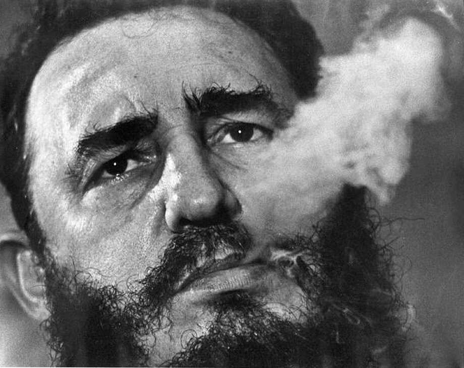 In this March 1985 file photo, Cuba's leader Fidel Castro exhales cigar smoke during an interview at the presidential palace in Havana, Cuba. Castro has died at age 90. President Raul Castro said on state television that his older brother died late Friday, Nov. 25, 2016. Photo: (AP Photo/Charles Tasnadi, File)