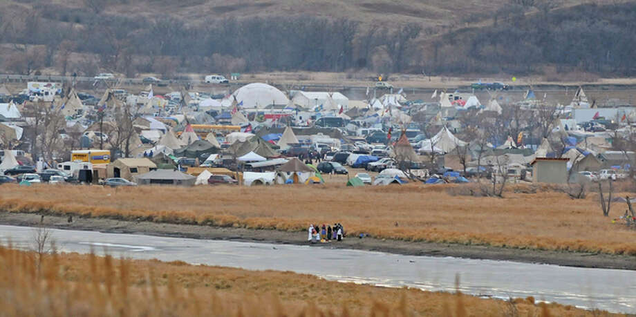 In this Nov. 24 photo, people stand on the edge of Cantapeta Creek near the growing Sacred Stones Overflow Protest Camp in Morton County, North Dakota. The leader of the Cheyenne River Sioux in South Dakota is calling for all opponents of the Dakota Access oil pipeline to boycott businesses in North Dakota's capital city. Photo: (Tom Stromme/Bismarck Tribune Via AP)