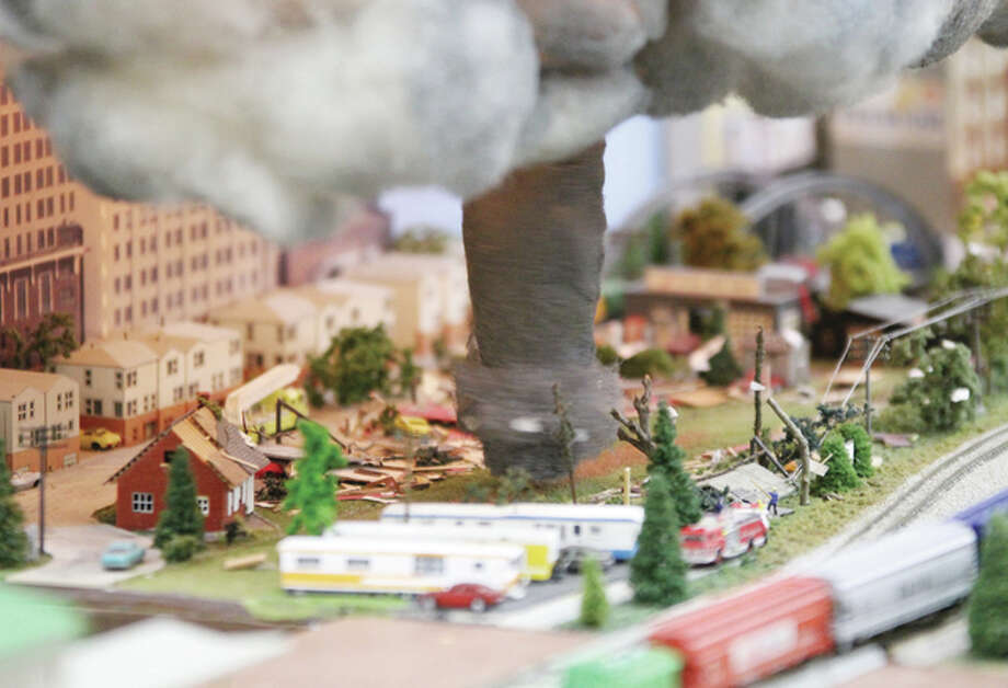 A tornado comes down from the clouds to wreak havoc on a model train layout at the Great Train Expo Saturday at the Gateway Center in Collinsville. The tornado, on an N-scale track layout, operates mechanically, spinning around as it works its way through the scene. Photo: Scott Cousins/The Telegraph