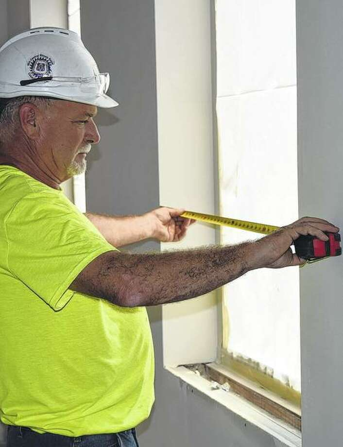Mike Lovekamp of Murrayville, job supervisor for R.D. Lawrence, measures a window opening Thursday in the new addition to The Farmers State Bank & Trust Co.'s West Morton Avenue location. Work on the addition and remodeling of the existing bank building are scheduled to be completed in early November. Photo: Greg Olson | Journal-Courier