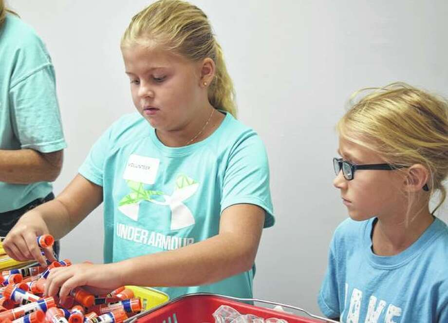 Laci Fearneyhough (left), 8, and Lindsey Reter, 6, help hand out school supplies Friday during the 7th Annual Back to School Bash at the Outreach Community Center in Winchester. Photo: Samantha McDaniel-Ogletree | Journal-Courier