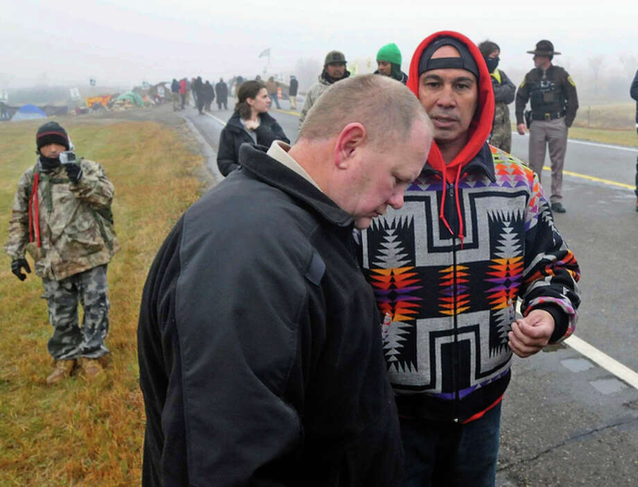 In this Oct. 26, 2016 file photo, Morton County Sheriff Kyle Kirchmeier, front, listens to Brian Wesley Horinek, of Oklahoma, outside the New Camp on Pipeline Easement in North Dakota. Kirchmeier, who has led the police response to the Dakota Access oil pipeline, is a law enforcement lifer, a veteran of the North Dakota State Patrol and National Guard before being elected to his first term as Morton County sheriff. Photo: (Tom Stromme/The Bismarck Tribune Via AP, File)