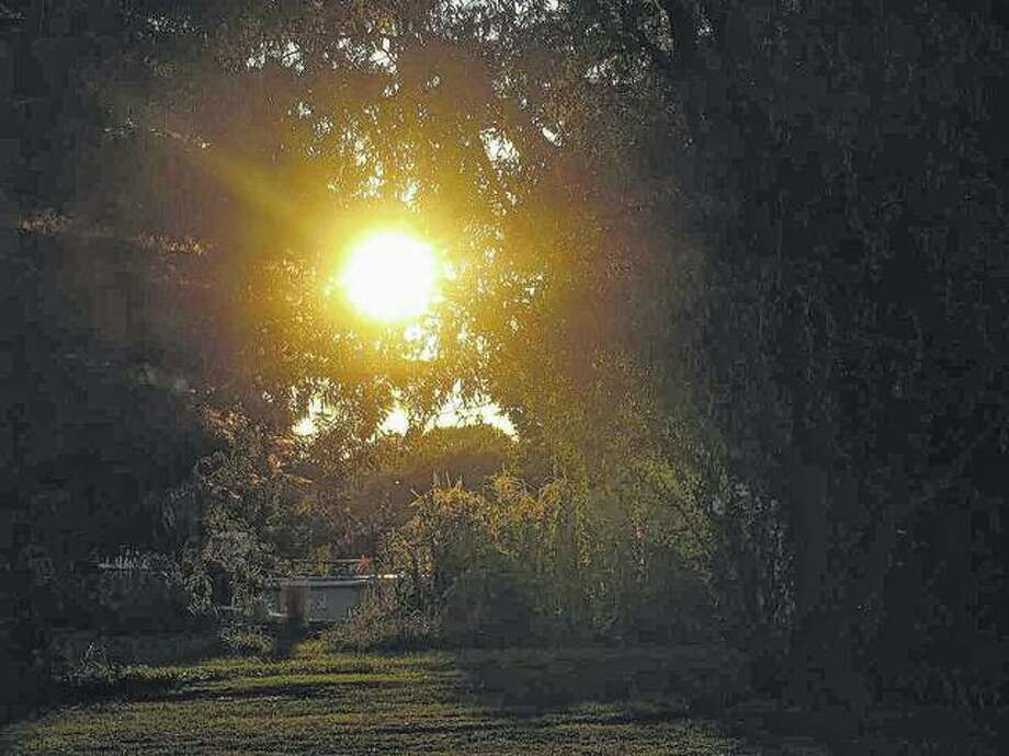 The setting sun appears to create a path across a yard in Scottville.