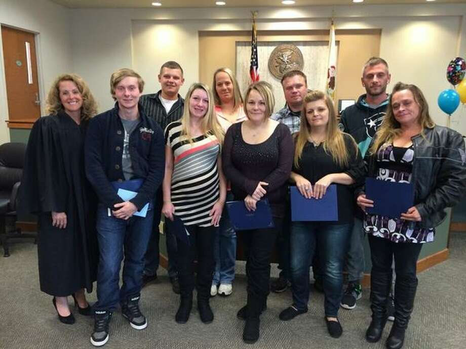 Circuit Judge Kyle Napp, far left, stands with the 11 drug court graduates Tuesday.