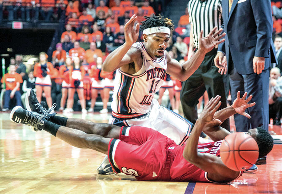Illinois guard Tracy Abrams (13) and North Carolina State guard Markell Johnson (11) battle for the ball Tuesday night in Champaign. Photo: AP