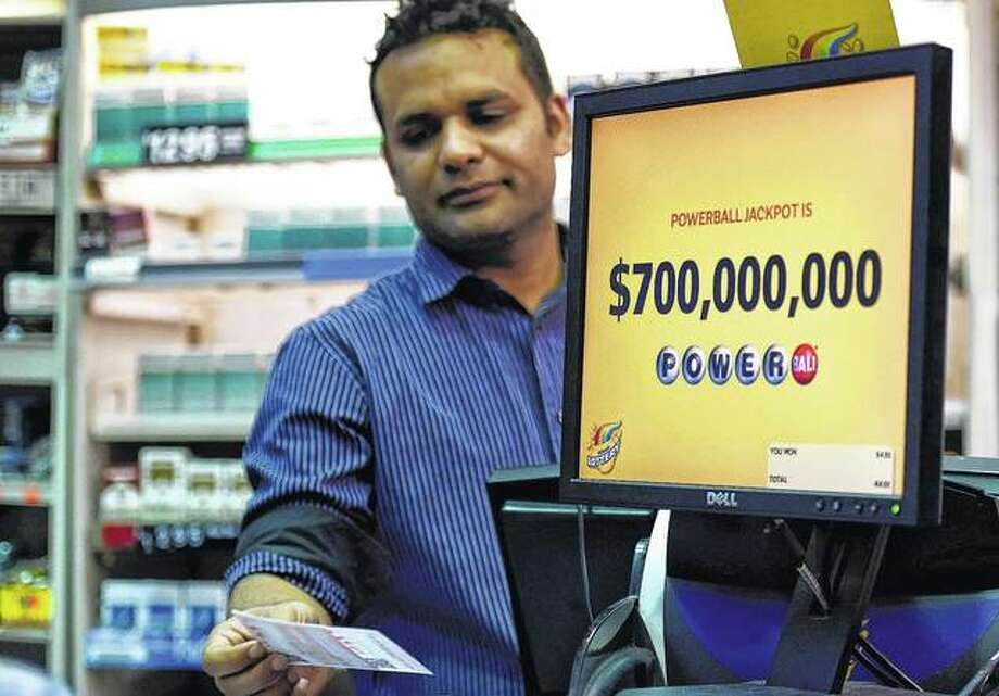 Screens display the lottery prizes as store clerk Malik Imran serves a customer Tuesday in Chicago. Officials estimate the jackpot for tonight's Powerball lottery game at more than $700 million, making it the second-largest in history.