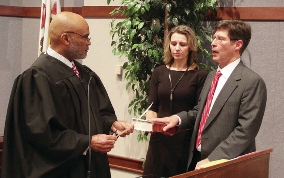 New Madison County Board Chairman Kurt Prenzler is sworn in Monday morning in the county board room. by Associate Judge Luther Simmons. Holding the bible is Prenzler's wife, Rita Prenzler.