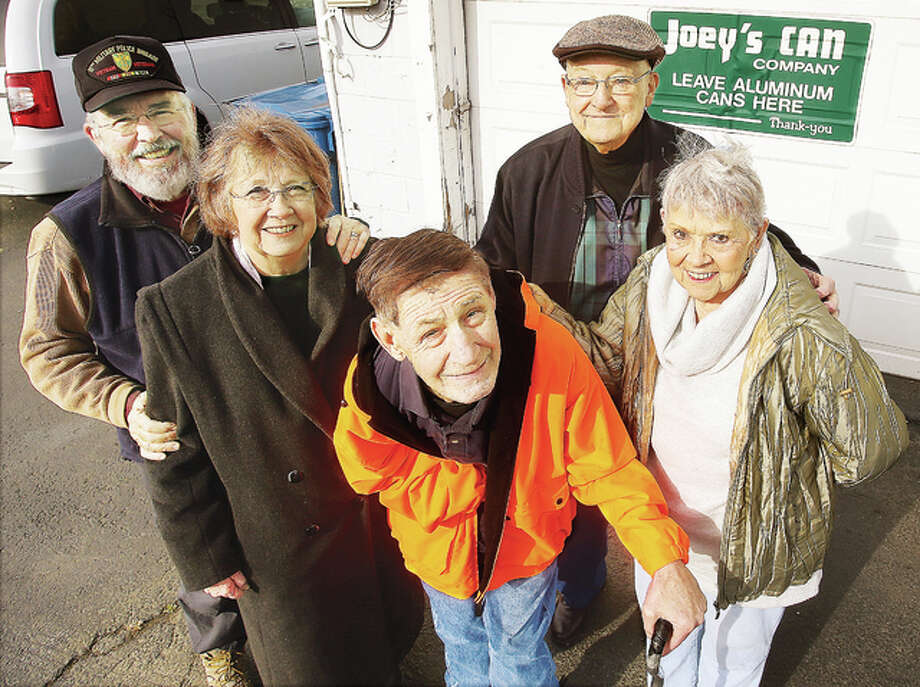 Charley Moyer, center, perhaps Upper Alton's most famous citizen, is retiring from a lifetime of collecting aluminum cans under his more well-known business name of Joey's Can Co. For decades, Charley, who has cerebral palsy, has been a fixture of the community, walking and later riding his cart and three- and four-wheeled cycles to collect discarded cans. Dale and Carol Neudecker, right, have taken care of Charley for more than 30 years. Charley will have a new home with Pat and Roger Lowery, left, who are taking him to Wilmington, North Carolina.