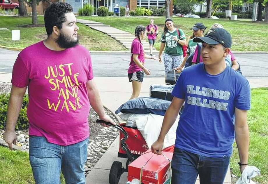 Josh Damotte (left), an Illinois College junior from Virginia, helps IC freshman Ulises Izquierdo of Chicago carry his belongings into a residence hall Thursday during the college's move-in day.