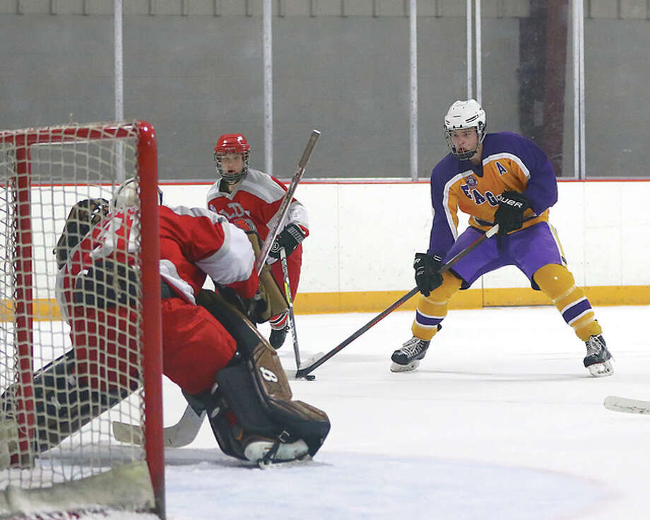 Bethalto's Joseph Watson, right, scored four goals in his team's 9-2 win over Alton Tuesday night at the East Alton Ice Arena. Watson is shown skating in on Alton goalie Caleb Currie in action earlier this season. Photo: Billy Hurst File Photo | For The Telegraph