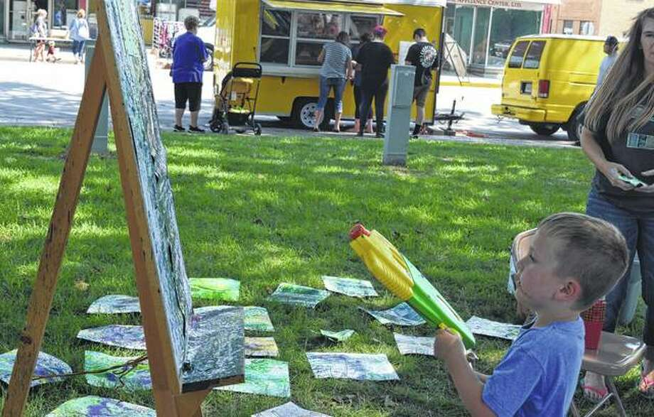 Noah Coats, 4, son of Erin and Seth Coats of Beardstown uses a water gun to spray paint onto a canvas during the Art in the Park and Taste of Beardstown Saturday. Photo: Samantha McDaniel-Ogletree | Journal-Courier