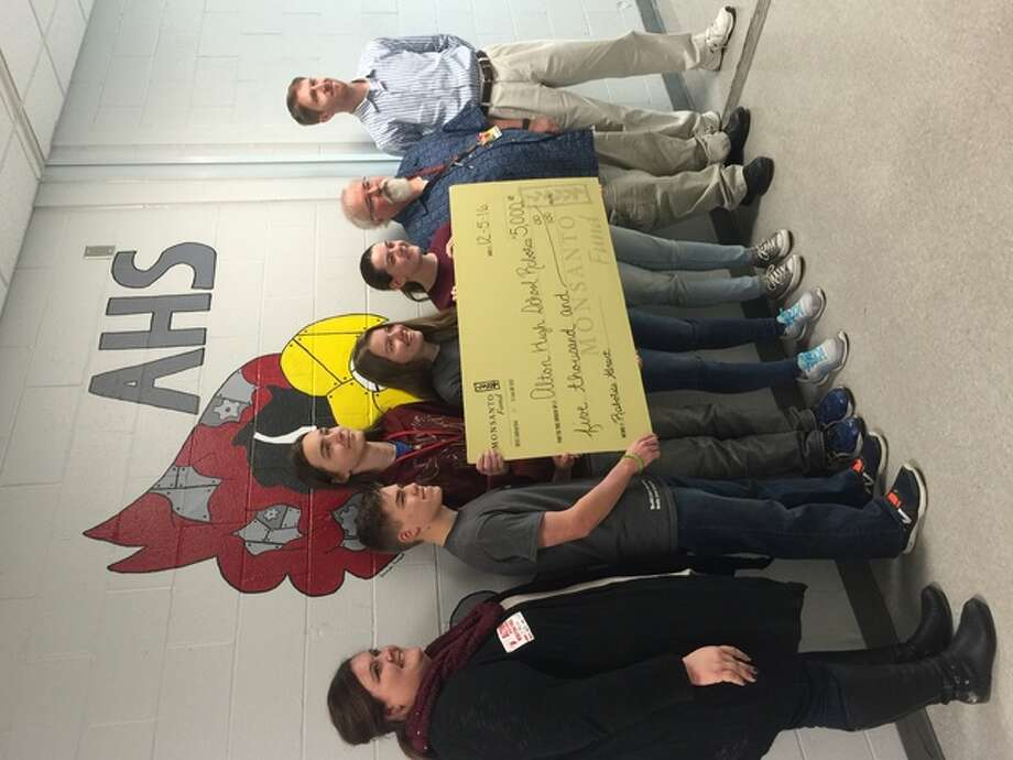 Alton High School Robotics Team members and representatives from Monsanto pose for a picture with the $5,000 grant check from the company to the club. The one-time grant will be used to purchase equipment for an upcoming competition.