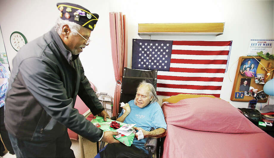 Alton American Legion Post 354 member Rick Plunkett, left, gives a gift to U.S. Army Korean War veteran Alex Christian, right, next to Christian's bed in the Rosewood Care Center on Humbert Road in Alton Wednesday. Members of the American Legion post were handing out gifts to veterans at multiple locations as a way to remember the 75th anniversary of the Japanese attack on the U.S. Pacific Fleet anchored at Pearl Harbor, Hawaii.