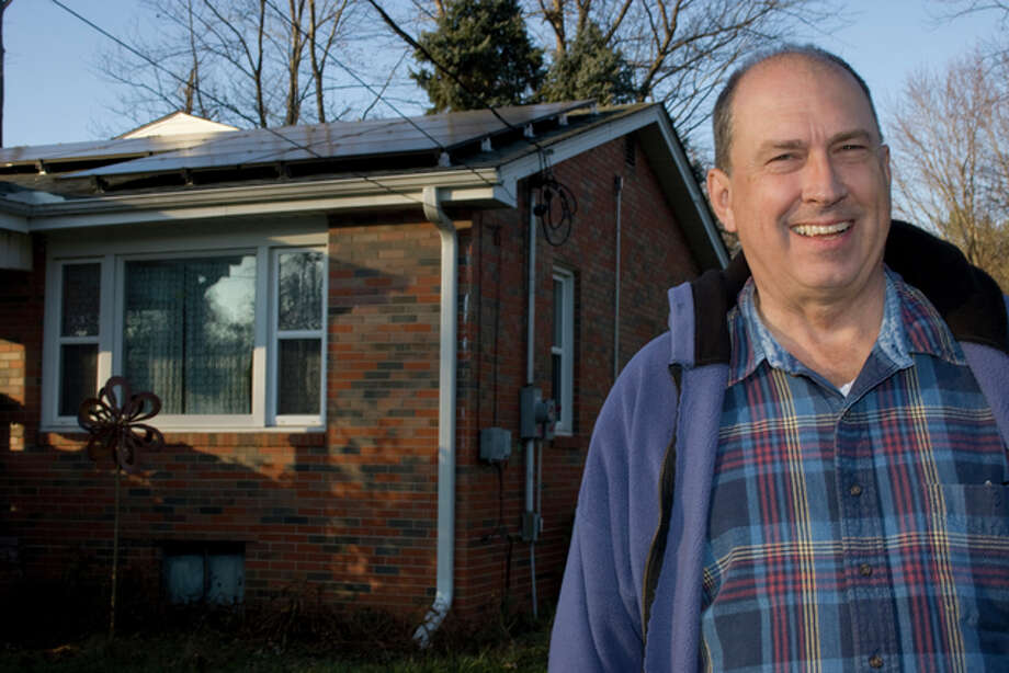 Mark Stewart stands next to his Godfrey home, which now supports an array of solar panels, nearly eliminating his summer electric bill.