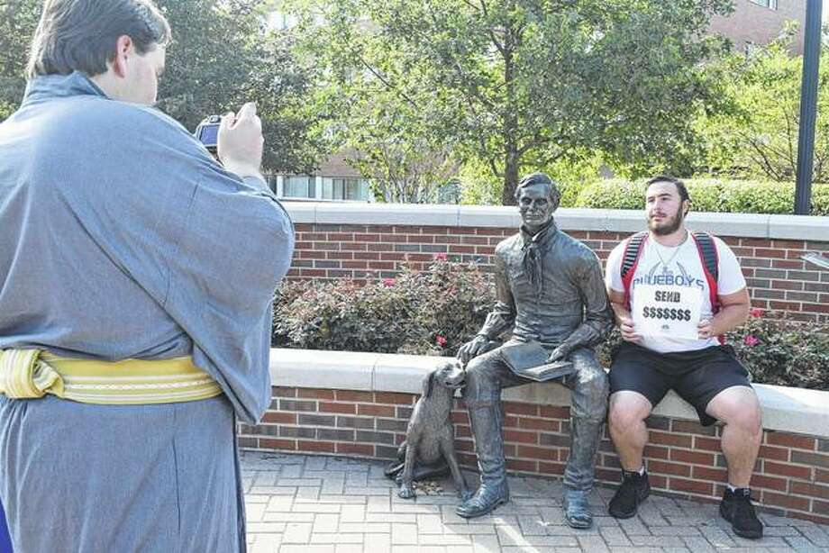 Illinois College junior Joshua Condon takes a picture of freshman David Dellit alongside an Abraham Lincoln statue in the Steuer Walkway on campus Tuesday. It has become a tradition for students at the college to take their picture with the president during the first full day of classes. Photo: Samantha McDaniel-Ogletree | Journal-Courier