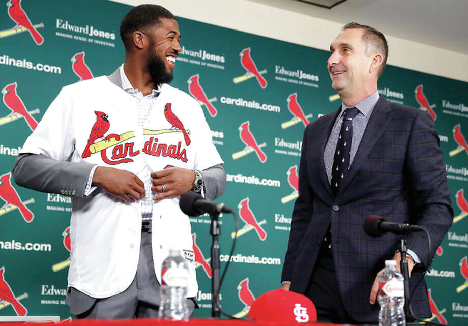 Cardinals general manager John Mozeliak, right, watches as Dexter Fowler puts a Cardinals jersey during a Friday morning news conference at Busch Stadium announcing the signing of the free agent center fielder. Photo: AP