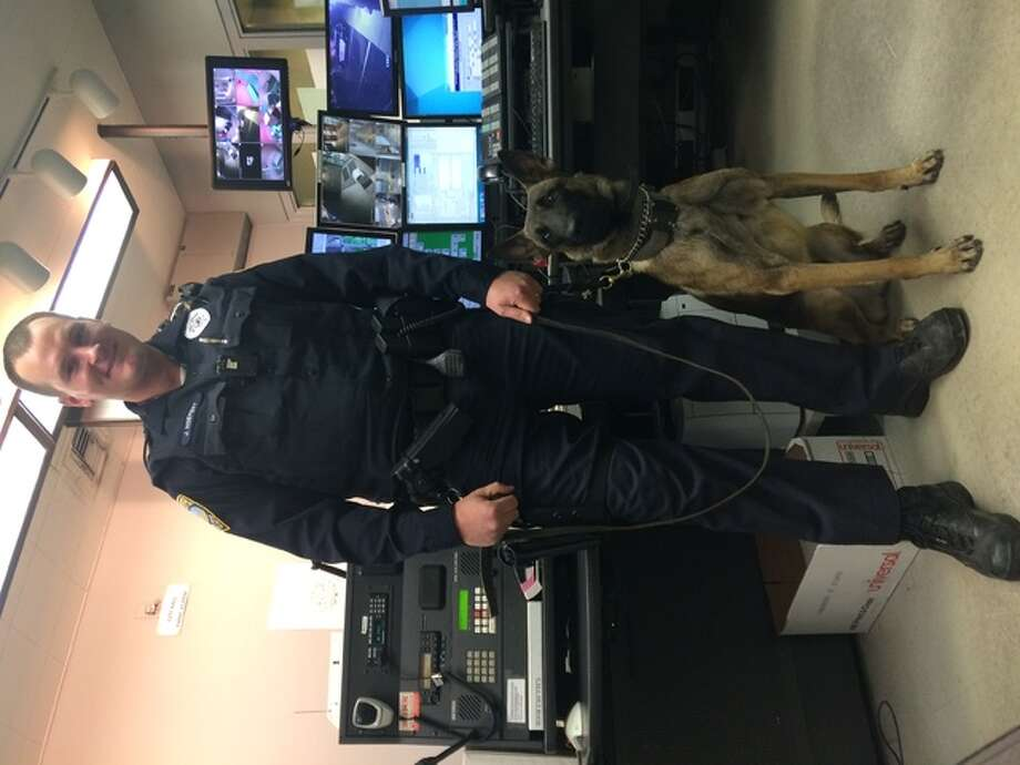 Alex Heeb/The Telegraph Wood River police officer John Hoefert stands with Bruno, Wood River's new K-9, in the dispatch center of the city's police department. The dog will make a significant contribution to officer safety, Hoefert said.