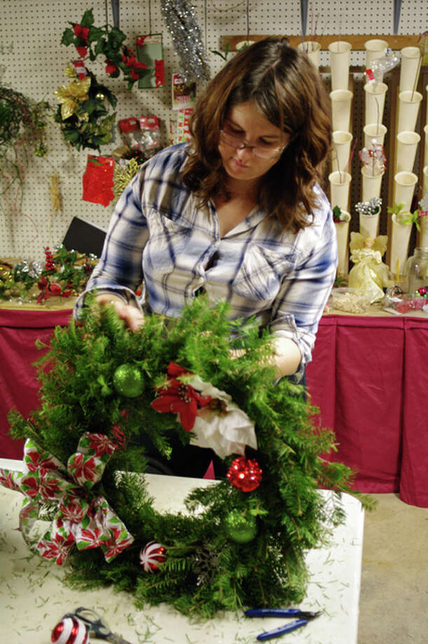 Kimberlee Boltz, of Brighton, constructs a natural wreath at Tangled Tinsel Christmas Tree Farm, the former Bartels Tree Farm, on Sunday. She was among those making wreaths as part of Girl Scout Service Unit 105 of Jersey-Calhoun counties.