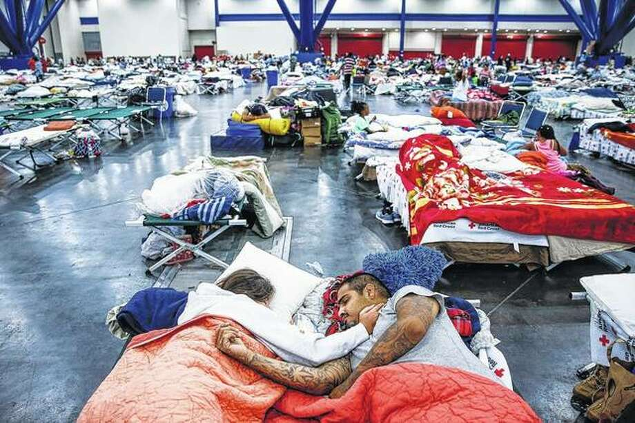 Tammy Dominguez (left) and her husband, Christopher Dominguez, sleep on cots at the George R. Brown Convention Center in Houston, where nearly 10,000 people were taking shelter after Hurricane Harvey. Others, like Jacksonville native Jordan Wilson, have found lodging in hotels while damage from the storm is assessed. Photo: Michael Ciaglo | Houston Chronicle (AP)