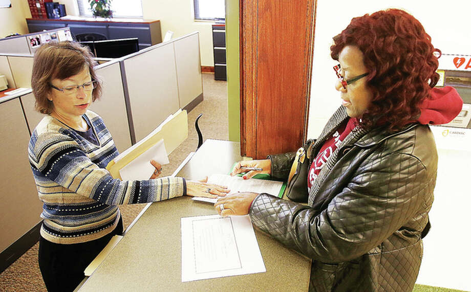 Cara Armstead, Alton deputy registrar, left, helps Rosetta Brown, right, with her paperwork Monday morning inside Alton City Hall, 101 E. Third Street, where candidates were turning in their nominating packets for various races next year. Brown is running for 4th Ward alderwoman in Alton.