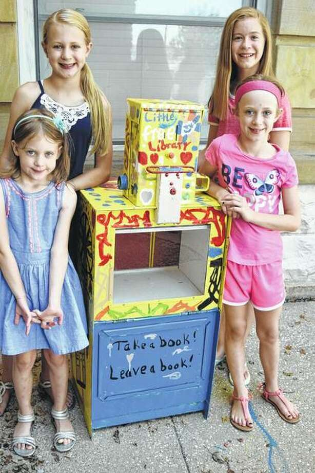 Thea Laumakis (from left), 5; Amanda Laumakis, 11; Abby Shireman, 11; and Lexi Laumakis, 8; stand with a free library box that they helped decorate. The box is a recycled Journal-Courier news rack and will hold books for a free library in front of the newspaper office.