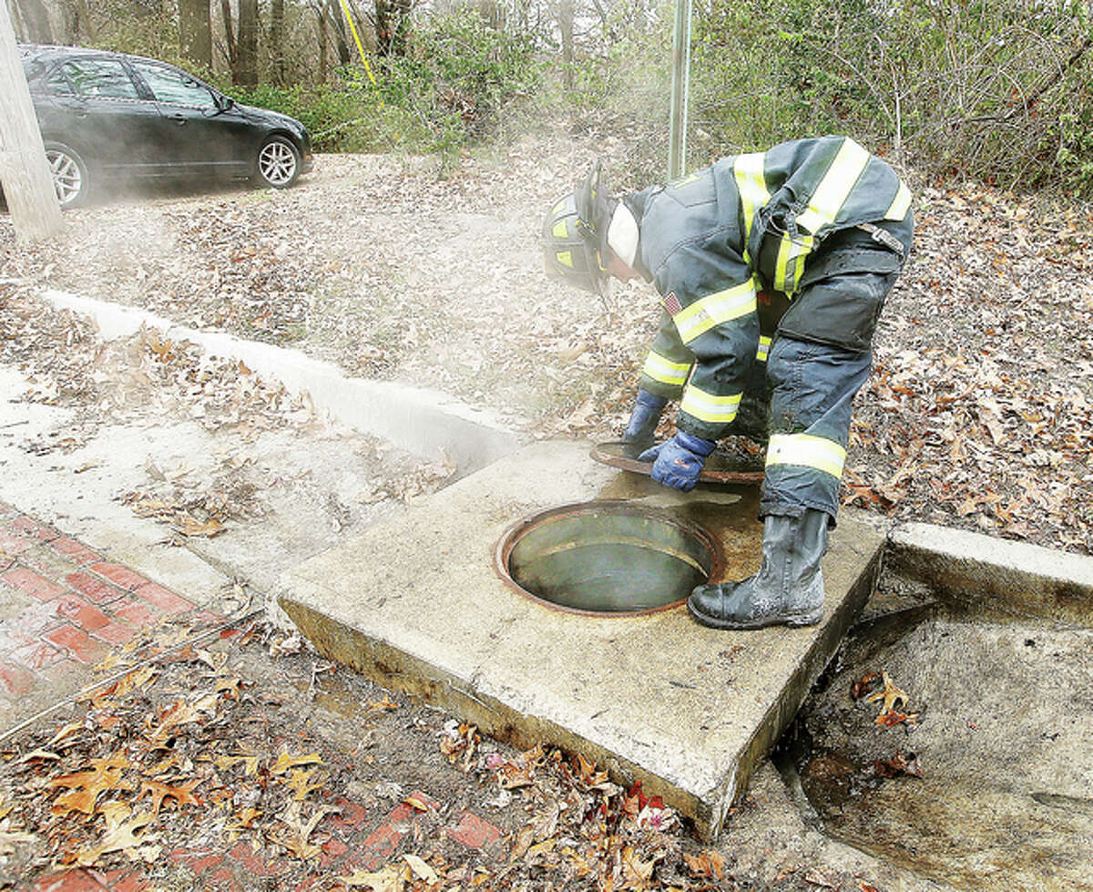 An Alton firefighter places the lid back on a storm sewer in the 600 block of Forest Drive in Alton Thursday after firefighters dumped water into the sewer in an effort to extinguish what fire officials said were leaves burning in the sewer. Steam was still rising out of the sewer. It was the second time firefighters were called to extinguish the stubborn fire Thursday.