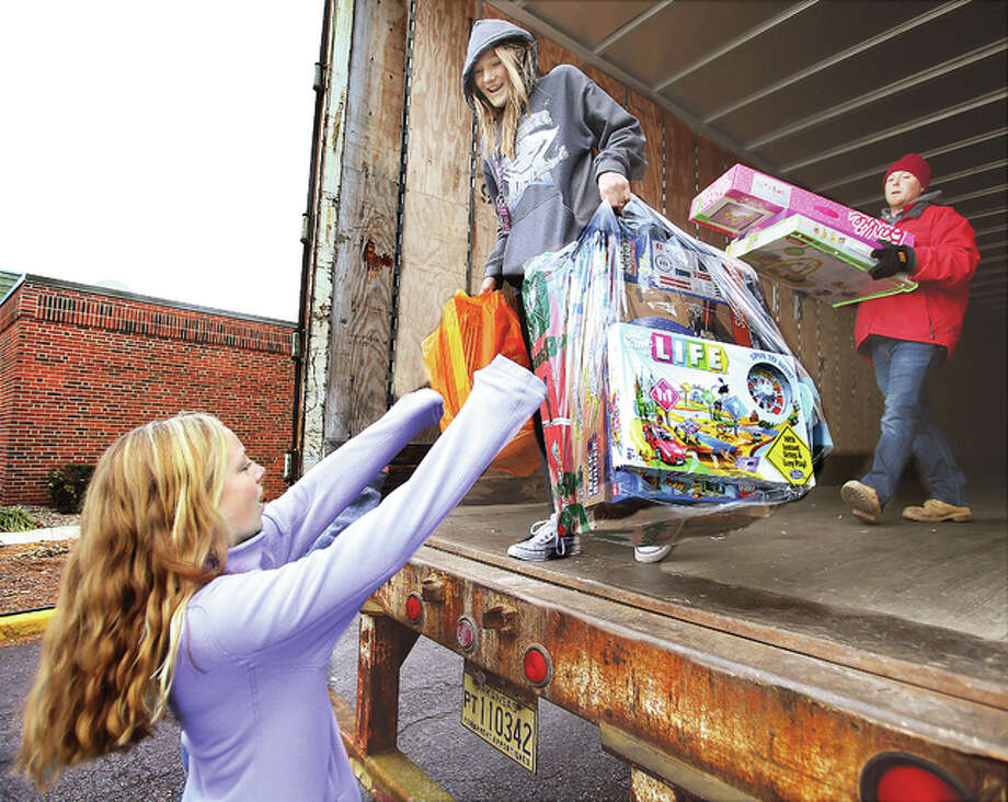 Volunteers, many of them area students, work to unload a truck filled with donated toys Thursday for the annual Community Christmas toy drive. The items were being taken into the Main Street United Methodist Church in Alton for sorting.