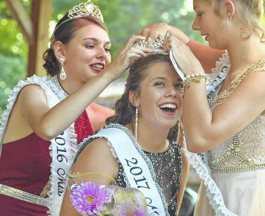 The 2017 Miss Arenzville Burgoo Hailey Stock (center) gets crowned by 2016 Miss Arenzville Burgoo Abigail Link (left) and 2016 Junior Miss Arenzville Burgoo Brooklynn Bateman Friday during the 2017 Arenzville Burgoo. Photo: Samantha McDaniel-Ogletree | Journal-Courier