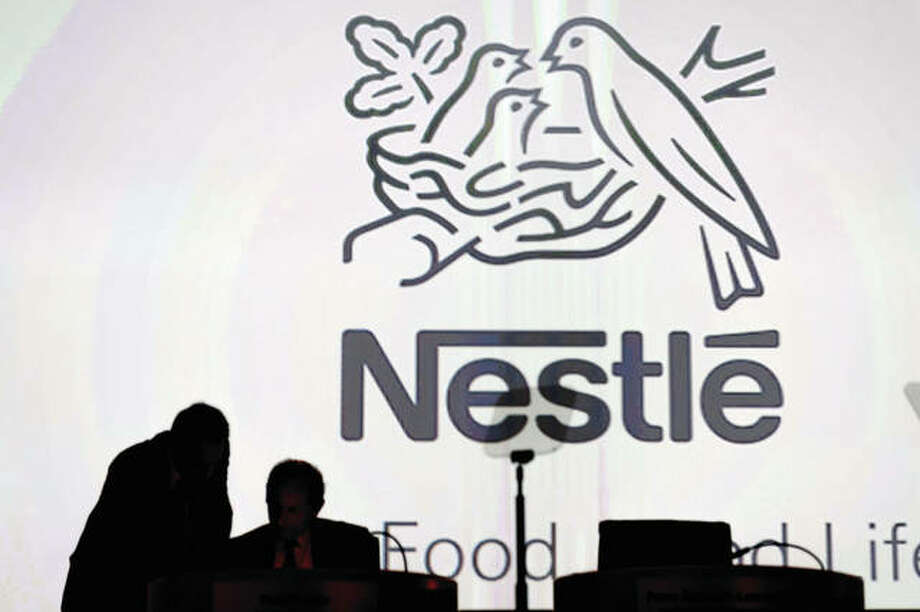 Directors speak in front of the Nestle's logo during the general meeting of Nestle Group in Lausanne, Switzerland. The world's biggest food and drinks company says it is buying husband-and-wife startup Sweet Earth, which sells frozen burritos stuffed with quinoa, beans and other vegetarian ingredients. Photo: Laurent Gillieron | Keystone (AP)
