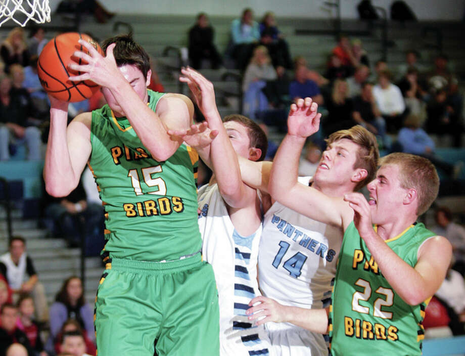 Southwestern's Collin Baumgartner pulls a rebound away from (from left) Jersey's Jacob Ridenhour, Drew Sauerwein (14) and Piasa Birds teammate Ben Lowis Friday night in Jerseyville. Photo: James B. Ritter | For The Telegraph