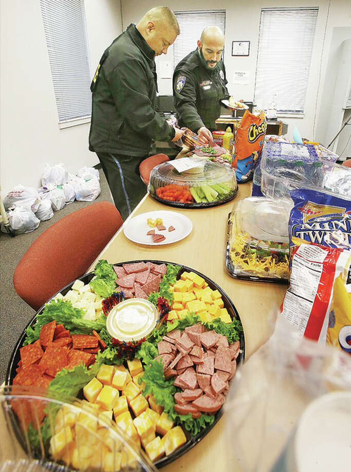 Alton Police Lt. Dan Rauschkolb, left, and officer Sam Riney make themselves some lunch Friday at the Alton Law Enforcement Center. The food was provided by nurses from Alton Memorial Hospital, some from the Obstetric Department, as a way of saying thank you to officers for helping to keep them and the community safe. Photo: John Badman|The Telegraph