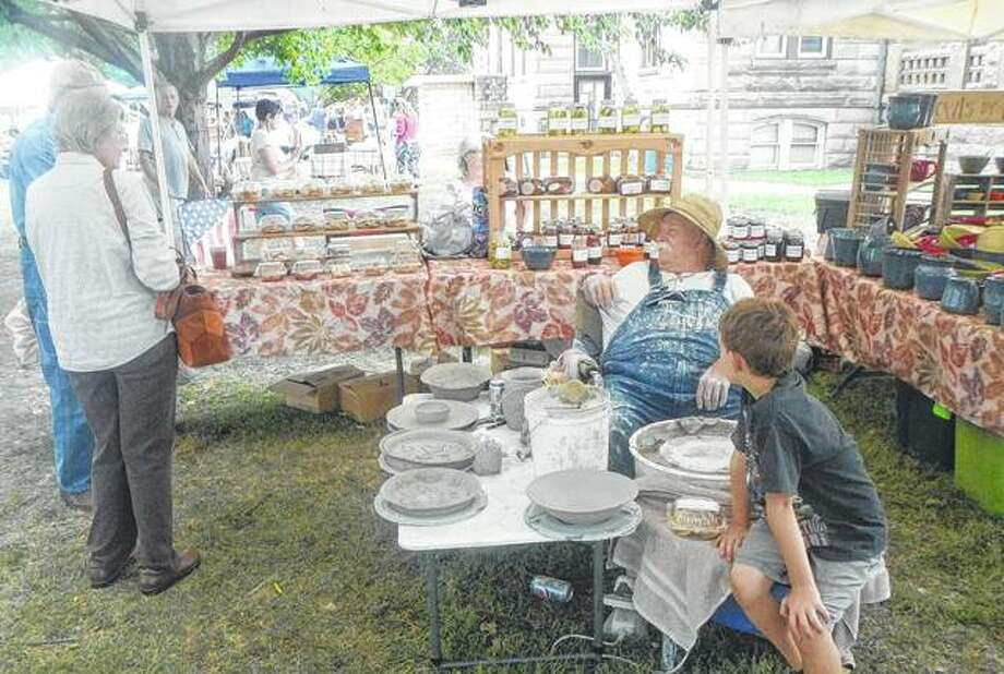 Bob Sancamper talks to visitors Sunday on the courthouse lawn in Carrollton during Greene County Days. Sancamper demonstrated his pottery wheel and had a variety of his Bowls by Bob wares available. The yearly celebration draws thousands to different locations throughout Greene County for food, vendors and entertainment.