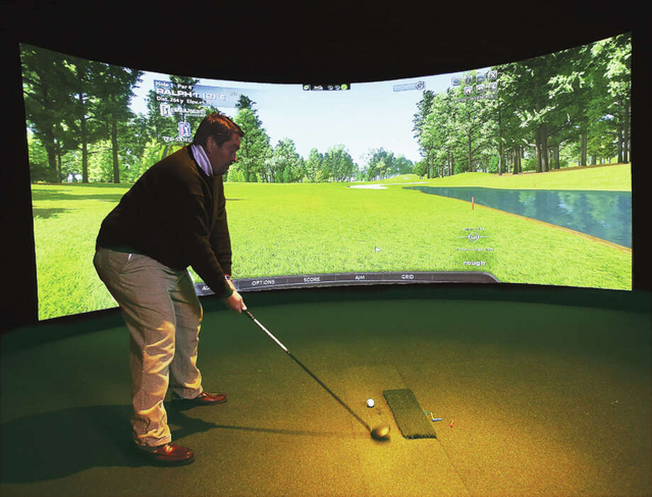 John Badman|The Telegraph Ralph Smith, chef at Roper's Regal Beagal restaurant in Godfrey, tries out one of the two new golf simulators constructed in a building behind the outdoor patio area of the restaurant. The simulators will allow you to choose many different world famous golf courses to play on. FLUSH FROM STORY PLEASE.