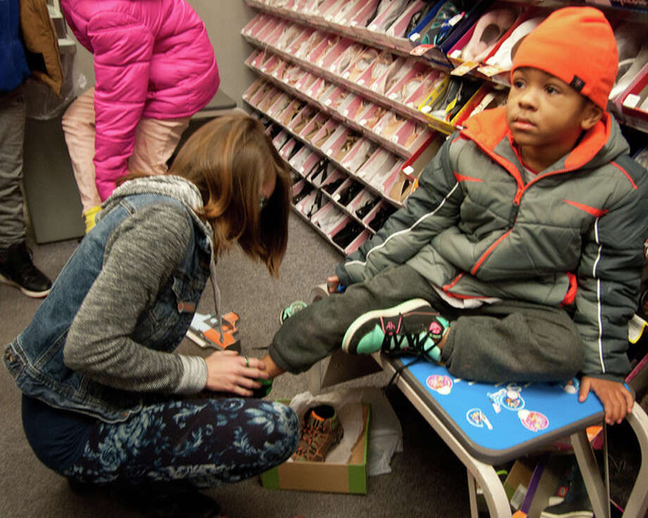 Josie Bregenzer helps 7-year-old Seven Keyhea put on a pair of shoes. President James Gray and the Alton NAACP helped purchase 36 new pairs of shoes for kids from the Alton public housing community, and some that were selected by people on the housing committee.