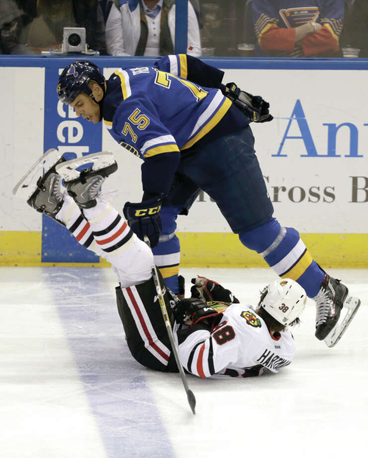 The Blues' Ryan Reaves (top) levels the Blackhawks' Ryan Hartman in the third period of the Blues' 6-4 loss Saturday night in St. Louis. Photo: Associated Press