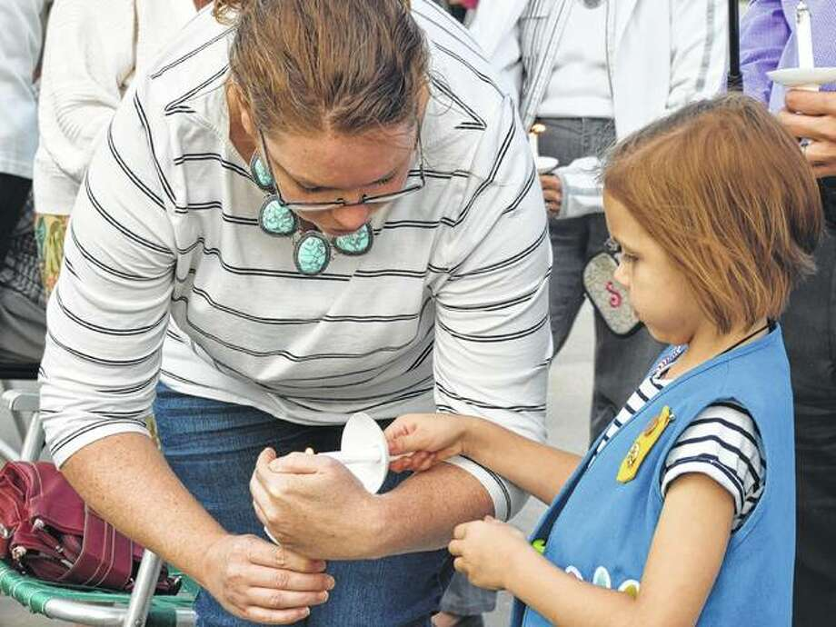 Siobhan Warren protects the flame on her candle so her daughter, Lydia Warren, 6, can light her own candle Monday during the candlelight vigil after the September 11 memorial ceremony on the downtown Jacksonville square. Photo: Samantha McDaniel-Ogletree | Journal-Courier