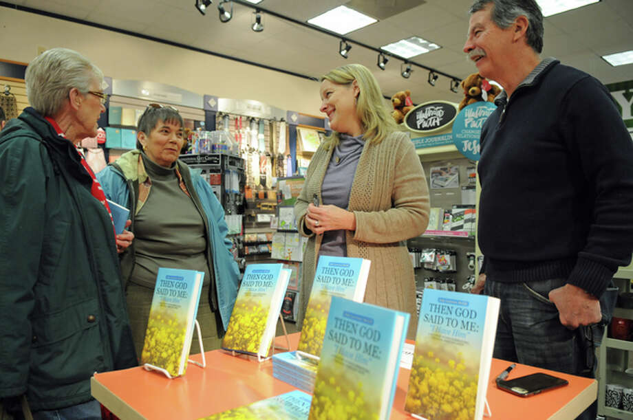 """Jeannine Bonine and Monty Dixon, of Belleville, left, talk to Judy and Butch McGill, right, during Judy McGill's book-signing event Saturday at Family Christian store in Alton Square Mall for Judy's book, """"Then God Said to Me: 'I Have Him.'"""" Photo: David Blanchette