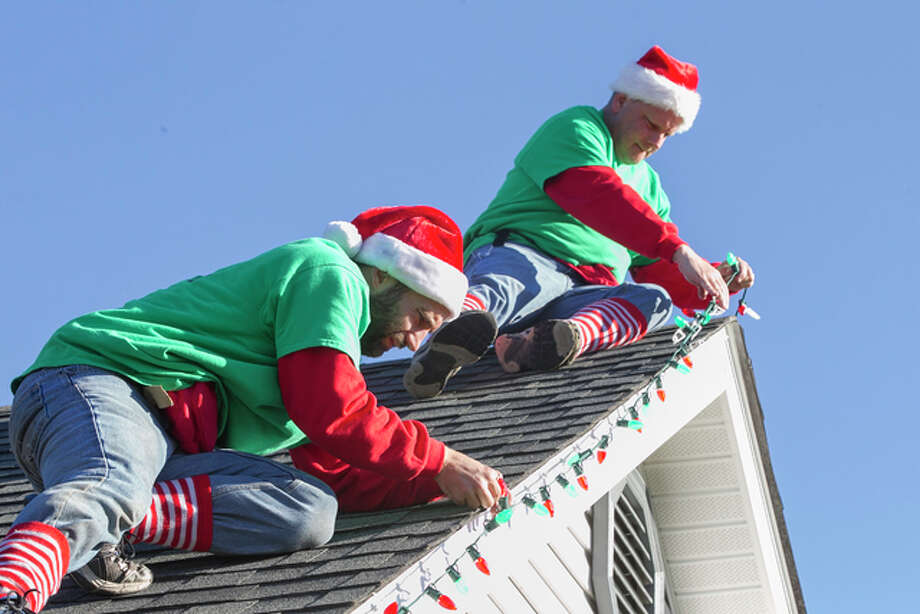 In this Nov. 19, 2016 photo, Ian Thurlow and Patrick Hulliung install lights on the roof of a home in Swansea, Ill. Jeannette Freed was a single mom and for many years and didn't have time to hang lights though her three children always wanted to see their home lit up. Today, she's married with a family home Belleville, Ill. So when she saw a pair of elves stringing lights on her neighbor's roof, she thought it was time. Those elves were Thurlow and Hulliung, co-owners of World Class Holiday Lighting in Belleville.