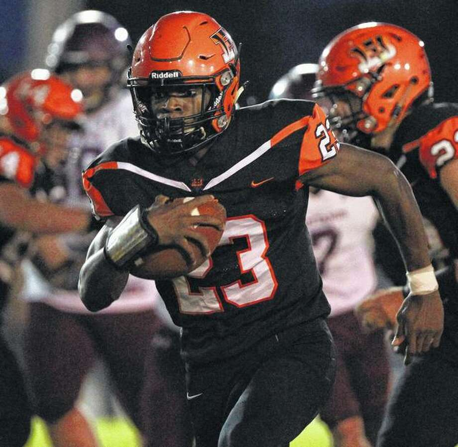 Beardstown's Pascal Guilavogui picks up yardage in a game against Mendon Unity Friday night in Beardstown. Photo: Dennis Mathes | Journal-Courier