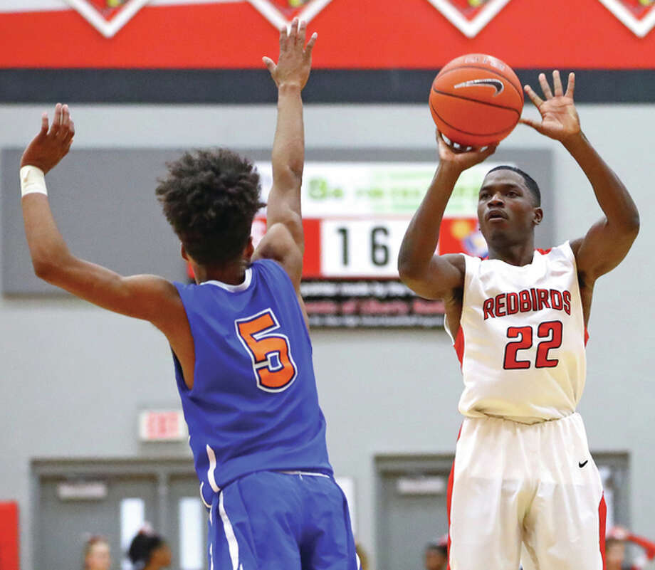 Alton's Kevin Caldwell (right), shown putting up a 3-pointer over East St. Louis' Zachery Forest during a SWC game Dec. 9 at Alton High, hit a long 3-pointer in the final seconds Friday night to lift the Redbirds to a SWC victory over the Lancers at Belleville East. Photo: Billy Hurst / For The Telegraph