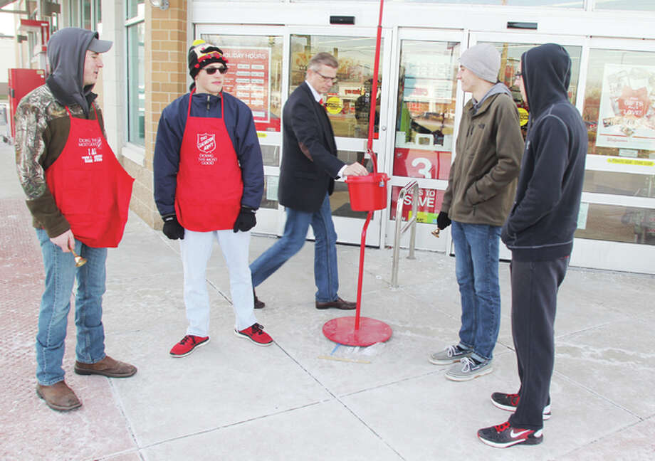 Chris Green, center, of Alton, puts some money in the Salvation Army kettle at the Walgreens on State Street as Alton High School National Honor Society members Noah Cash, left, Deven Long, Sam Gentalin and Alex Scyoc work as bell-ringers. The Salvation Army's annual kettle campaign is winding down and will end Saturday. This year's goal is $85,000.
