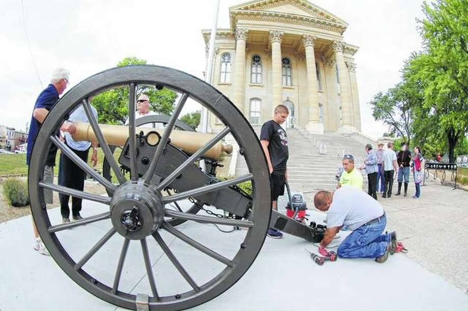 Workers from Koster Construction install brackets to hold a Civil War-era cannon in place in front of the Macoupin County Courthouse. The restored cannon was dedicated during a ceremony Sunday in Carlinville. Photo: Photo | David Blanchette