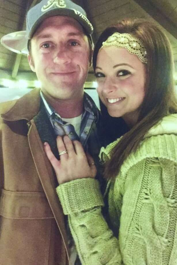 Newly engaged couple Brian Cline and ReeAnna Cottingham embrace, engagement ring on display, at the Bethalto Central Park Christmas Village in Bethalto's Central Park earlier this month.