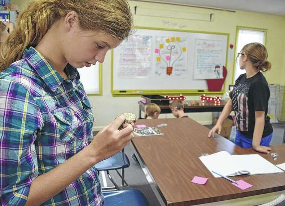 Kaitlyn Baker, an eigth-grader at Salem Lutheran School, examines a rock during science class. Photo: Samantha McDaniel-Ogletree | Journal-Courier