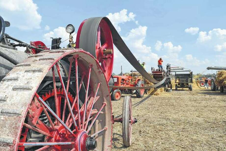 An antique steam traction engine (foreground) powers a separator as it threshes wheat during last year's Prairie Land Heritage Museum Fall Festival and Steam Show Days in South Jacksonville. This year's three-day event begins Friday. Photo: Greg Olson | Journal-Courier