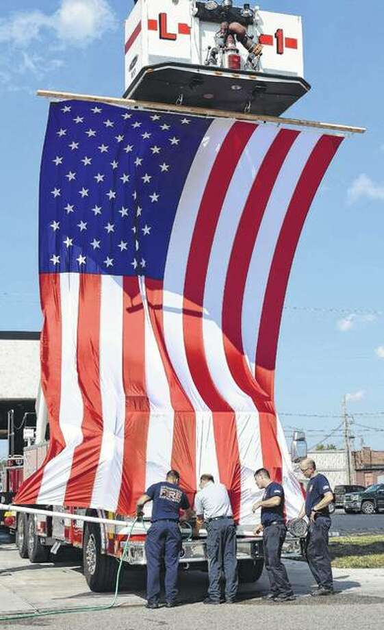 Members of the Jacksonville Fire Department unfurl a new American flag Wednesday. They were trying to find a way to weigh it down while it is on the truck. The flag will be attached to a ladder truck for special events. Photo: Samantha McDaniel-Ogletree | Journal-Courier