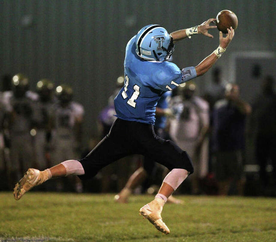 Triopia's Zach Thompson reaches out to catch a pass on a 64-yard catch-and-run for a touchdown during a win over Routt Thursday night at Triopia. Photo: Dennis Mathes | Journal-Courier