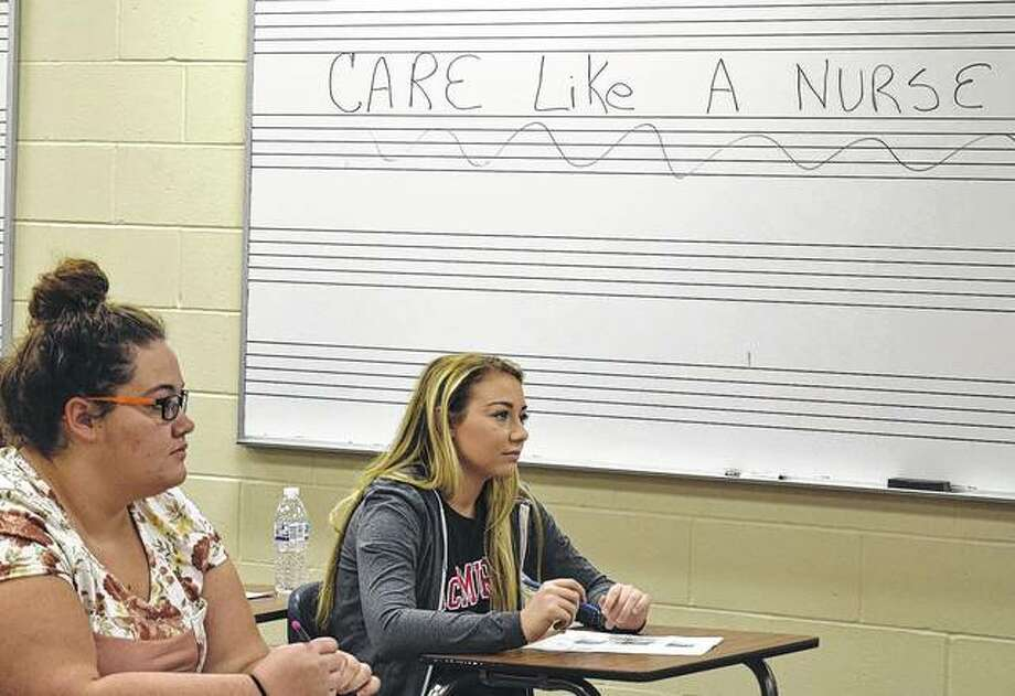 Emma Weller (left) and Juliana Russotto, both juniors in the MacMurray College nursing program, take notes Thursday during class. Photo: Samanatha McDaniel-Ogletree | Journal-Courier