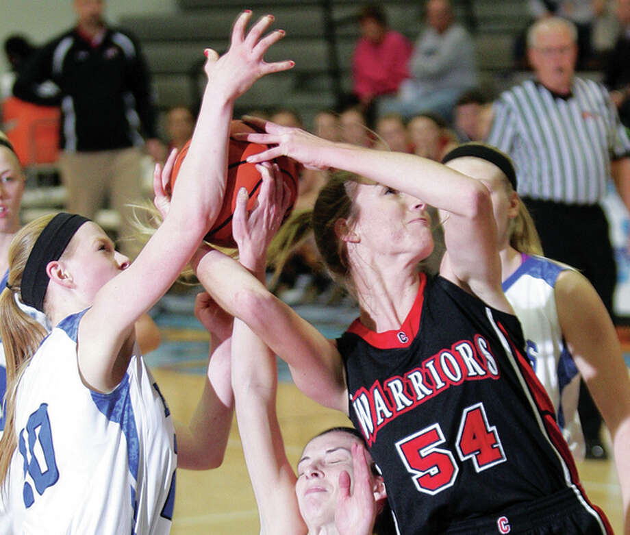 Calhoun's Grave Baalman grabs a rebound and goes up for a basket despite the defense of Brussels' Jackie Rose, left, and Baylee Kiel, lower center Tuesday in Jerseyville. Photo: James B. Ritter | For The Telegraph