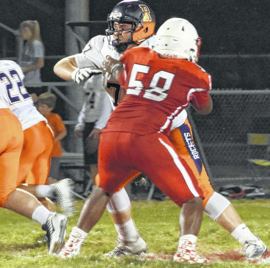 Jacksonville's DiMaggio Trotter holds off a Rochester lineman Friday night. Photo: Audrey Clayton | Journal-Courier